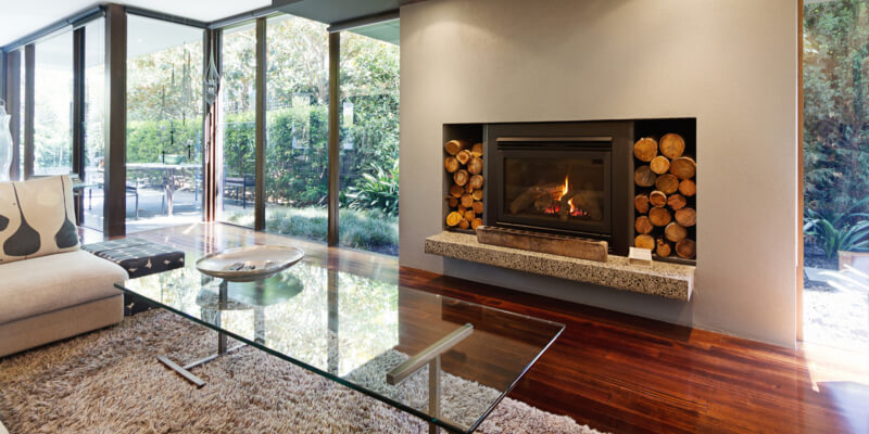 Bifold Doors in a living room with laminate floors. Fireplace burning and glass table in front of it.
