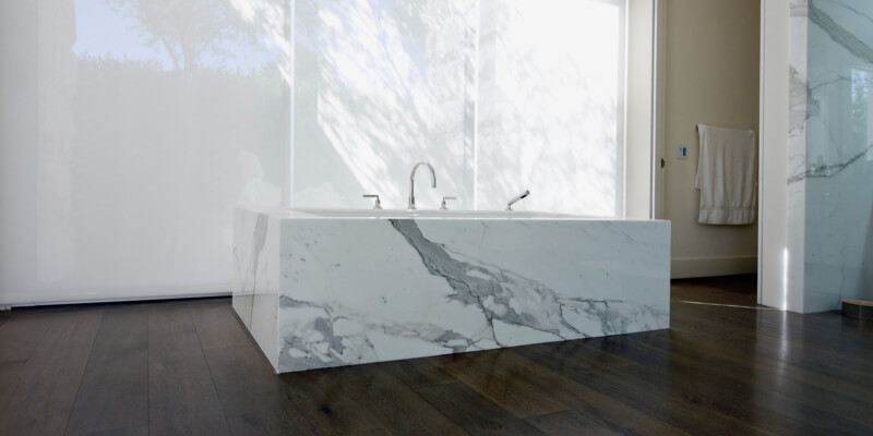 Low angle view of a modern bathroom with stand-alone marble clad tub, laminate floor and vertical shades