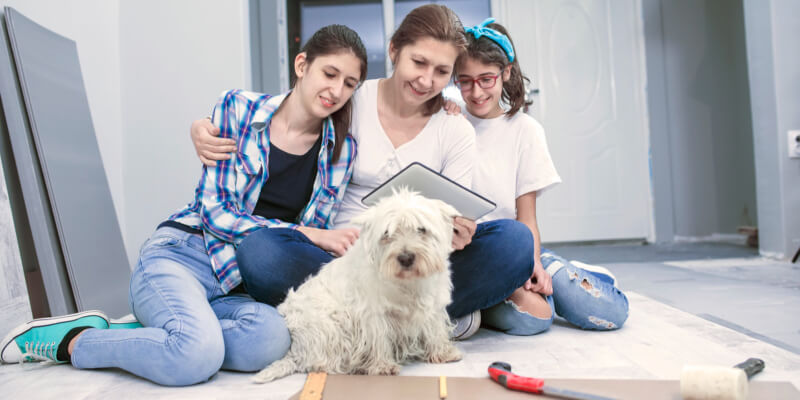 Middle age mother and her teenagers daughters with cute dog installing new wooden floor together