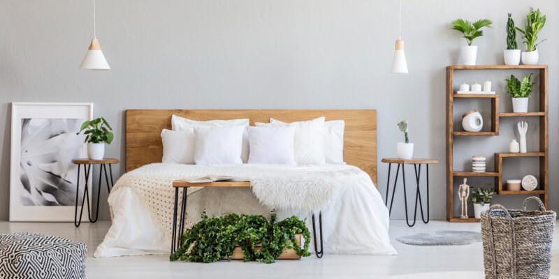 Patterned pouf and basket in bright bedroom interior with lamps and bed with laminate headboard