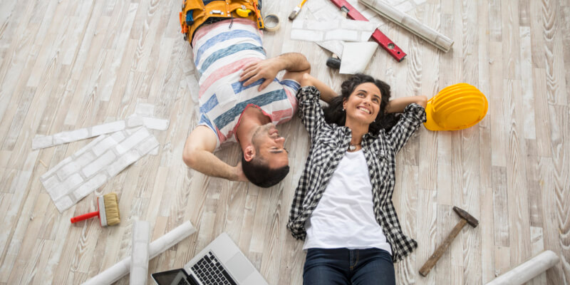 A couple lies on a laminate floor surrounded by tools, a laptop, and white paper
